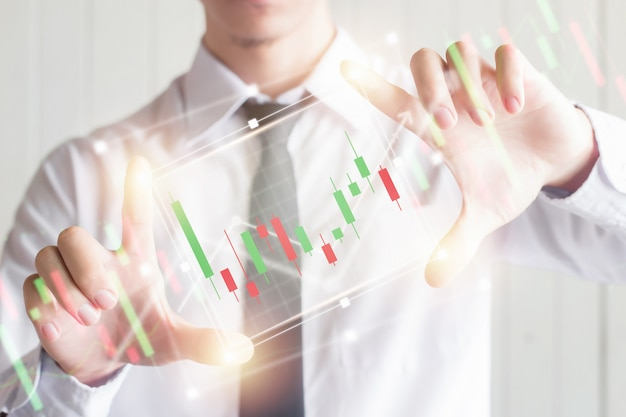 Het aziatische bedrijfs mannelijke gebruikende vinger breidt het digitale virtuele scherm met kandelaargrafiek, financieel en investeringsconcept uit Premium Foto
