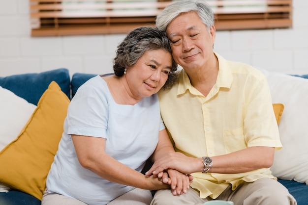 Het aziatische bejaarde paar die hun handen houden terwijl samen het nemen in woonkamer, paar die gelukkig aandeel voelen en steunt elkaar liggend op bank thuis. Gratis Foto