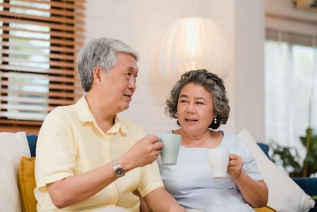 Het aziatische bejaarde paar die warme koffie drinken en samen in woonkamer thuis spreken, genieten het paar van liefdeogenblik terwijl het liggen op bank wanneer ontspannen thuis. Gratis Foto