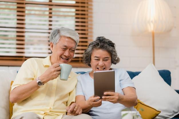 Het aziatische bejaarde paar gebruikend tablet en het drinken de koffie in woonkamer thuis, paar genieten liefde van ogenblik terwijl het liggen op bank wanneer ontspannen thuis. Gratis Foto