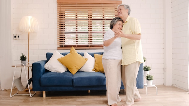 Het aziatische bejaarde paar samen dansen terwijl thuis aan muziek in woonkamer luister, het zoete paar geniet liefde van ogenblik terwijl het hebben van pret wanneer thuis ontspannen. Gratis Foto