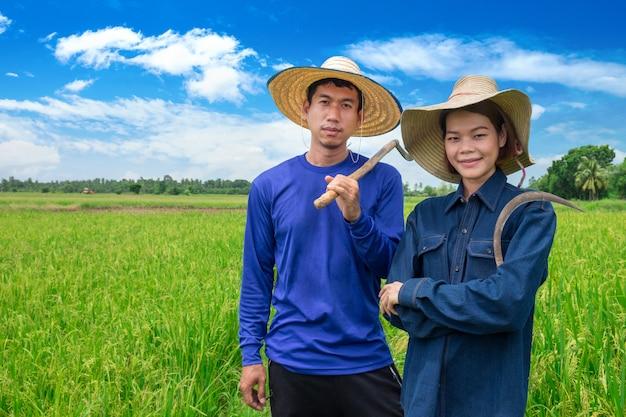 Het aziatische glimlachpaar van landbouwers houdt hulpmiddelen en status bij rijstlandbouwbedrijf Premium Foto