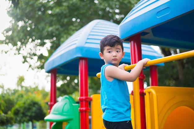 Het aziatische jong geitje spelen bij de speelplaats onder het zonlicht in de zomer Premium Foto