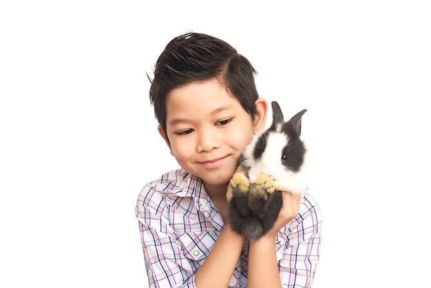 Het aziatische jong geitje spelen met mooi babykonijn dat over wit wordt geïsoleerd Gratis Foto