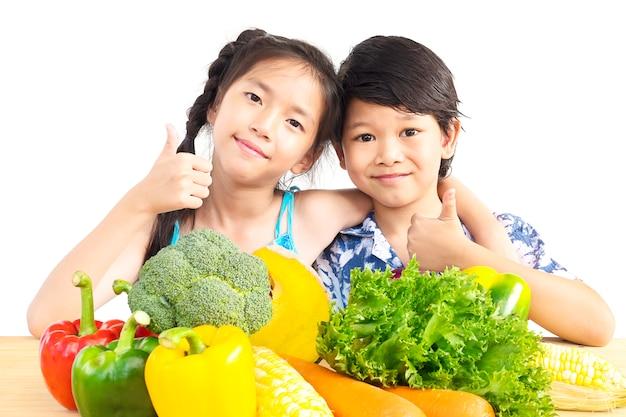 Het aziatische jongen en meisjes tonen geniet van uitdrukking met verse kleurrijke groenten Gratis Foto