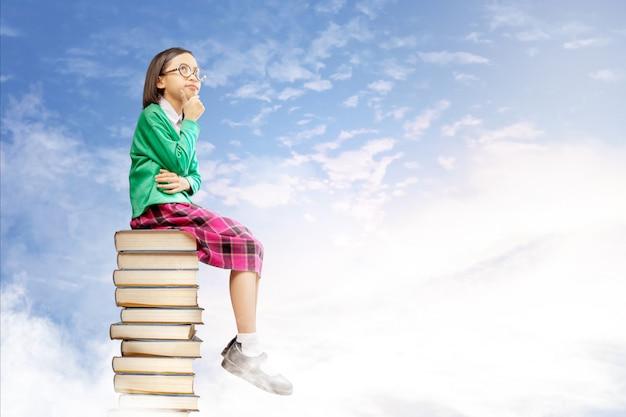 Het aziatische leuke meisje met glazen denkt terwijl het zitten op de stapel van boeken met blauwe hemel Premium Foto