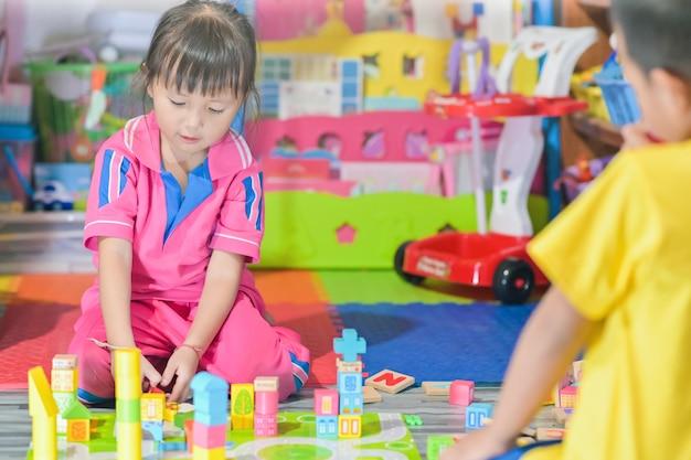 Het aziatische meisjekind spelen in ruimtespeelgoed voor kinderen ontwikkelt zich in kleuterschool, ook bekend als kleuterschool Premium Foto