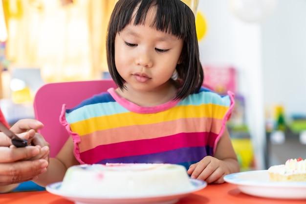 Het aziatische meisjesjonge geitje dat haar verjaardagstaart snijdt viert Premium Foto