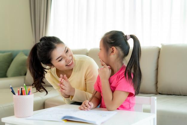Het aziatische moeder spelen met haar dochter die samen met kleurenpotloden thuis bij lijst in woonkamer trekken. ouderschap of liefde en binding expressie concept. Premium Foto