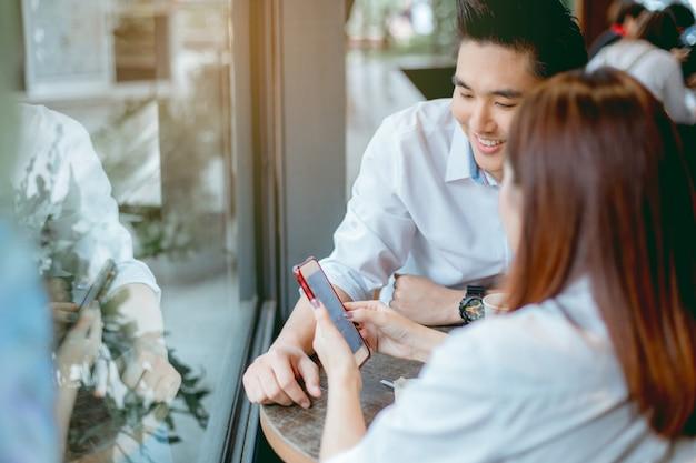 Het aziatische paar gebruikt smartphones samen. Premium Foto