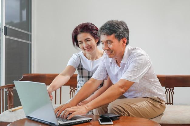 Het aziatische paar van middelbare leeftijd werkt vanuit huis Premium Foto