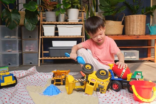 Het aziatische peuterjongen spelen met kinetisch zand thuis, kind het spelen met stuk speelgoed bouwmachines, montessori-onderwijs, creatief spel voor jonge geitjesconcept Premium Foto