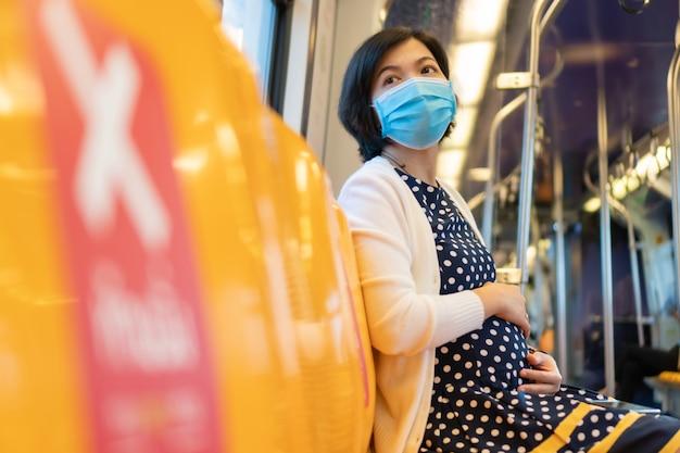 Het aziatische zwangere gezichtsmasker van de vrouwenslijtage zit in hemeltrein in het nieuwe normale leven Premium Foto