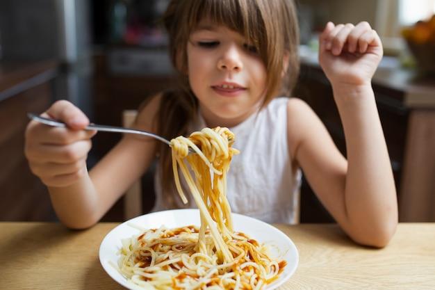 Het babymeisje dat van de close-up deegwarenschotel eet Gratis Foto