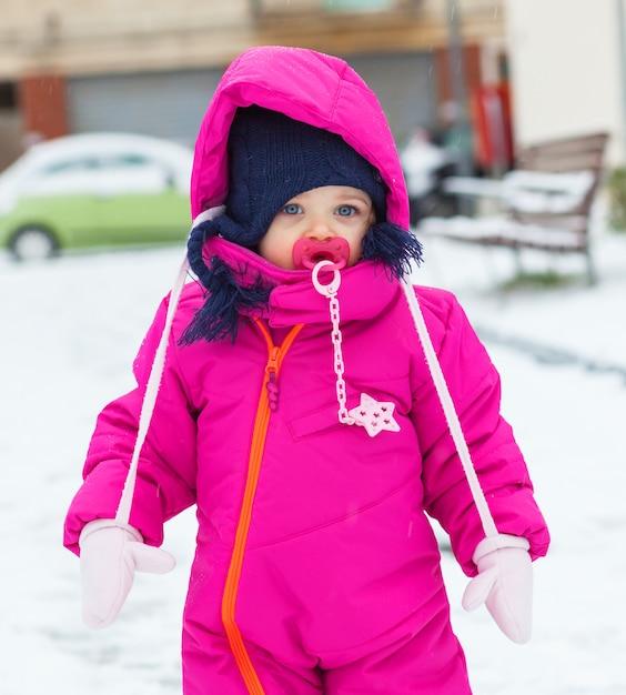 Het babymeisje van de peuter in een magenta sneeuwkostuum die op de sneeuw spelen. Premium Foto