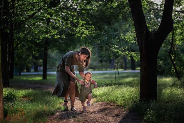 Het babymeisje zet de eerste stapjes, een jonge moeder die een kind bij de hand houdt, verzekert en helpt om langs het pad van het park te lopen tussen groene bomen en gras. ouderlijke zorg Premium Foto