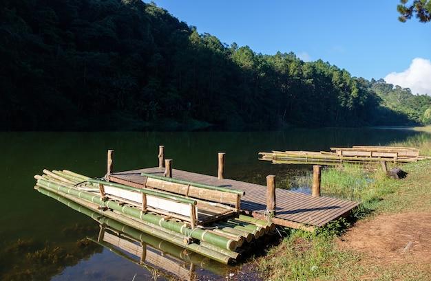 Het bamboevlot drijft bij de houten pier voor de toeristen Premium Foto
