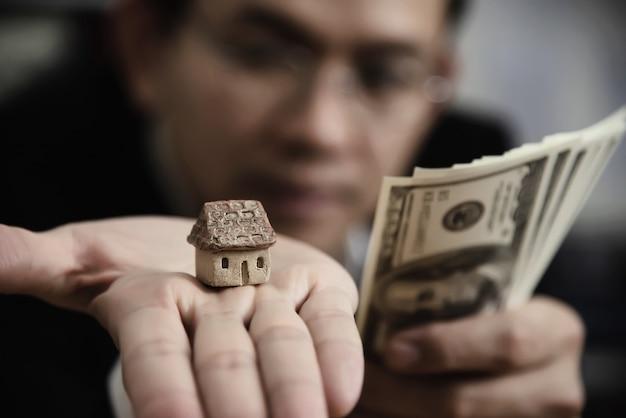 Het bankbiljet van het bedrijfsmensen toont geld maakt het financiële plan mensen uitnodigen om huis en auto te verkopen of te kopen - het monetaire kredietconcept van de leenkredietverzekering Gratis Foto
