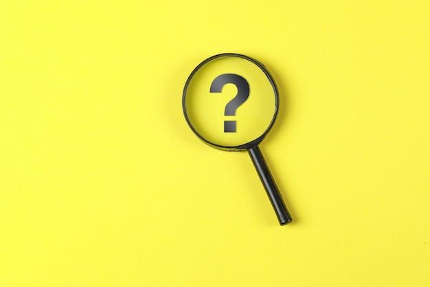 Het bedrijfs en financiële concept met vergrootglas, vraagteken op gele vlakte als achtergrond lag. Gratis Foto