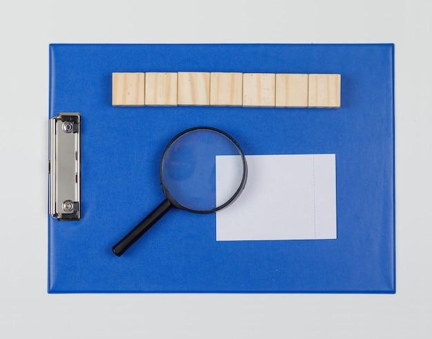 Het bedrijfsconcept met houten blokken, document folder, vergrootglas, kleverige nota op witte vlakte als achtergrond lag. Gratis Foto