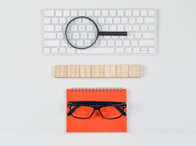 Het bedrijfsconcept met houten blokken, glazen, vergrootglas op toetsenbord op witte vlakte als achtergrond lag. Gratis Foto