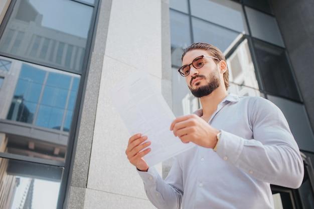 Het beeld van jonge modieuze mensentribune en stelt. hij kijkt door een zonnebril naar een wit stuk papier. guy is kalm, vredig en geconcentreerd. hij staat voor een glazen gebouw. Premium Foto