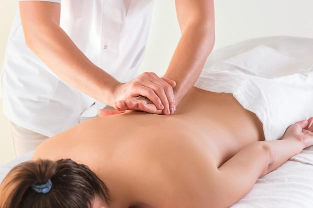Het beeld van mooie vrouw in massagesalon en mannelijke handen sluit omhoog Gratis Foto