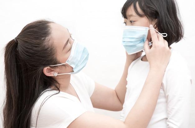 Het beeldgezicht van een jonge aziatische vrouw en familie die een masker dragen om ziektekiemen, giftige dampen en stof te voorkomen. preventie van bacteriële infectie corona-virus of covid 19 Premium Foto