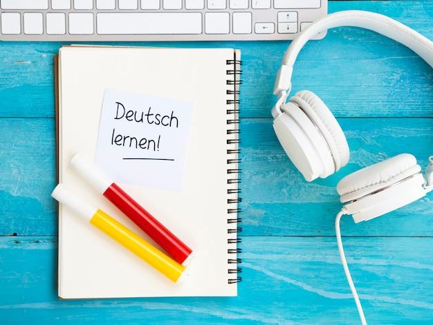 Het bestuderen van nieuwe taalhulpmiddelen op blauwe houten achtergrond Gratis Foto