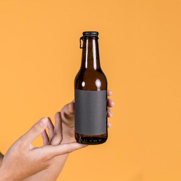 Het bierfles van de de handholding van de persoon over gele achtergrond Gratis Foto