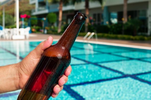 Het bierfles van de handholding bij pool Gratis Foto
