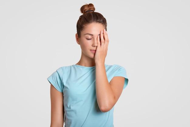 Het binnenschot van vermoeide sportvrouw behandelt gezicht met hand, gekleed in casual t-shirt, houdt ogen dicht, probeert geconcentreerd te zijn. vrouwelijke fitnesstrainer voelt zich uitgeput na aërobe trainingen, geïsoleerd Premium Foto