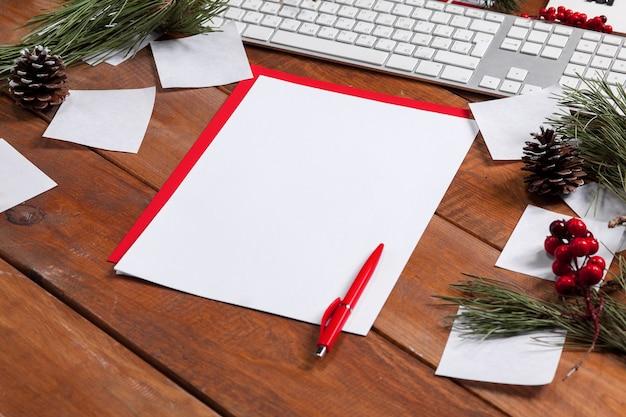 Het blanco vel papier op de houten tafel met een pen en kerstversiering. kerst mockup concept Gratis Foto
