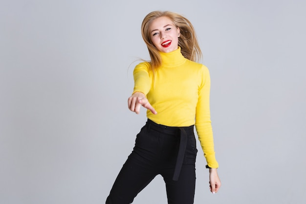 Het blije blondemeisje heeft pret dansende binnen richtend haar vinger rechtstreeks. Premium Foto