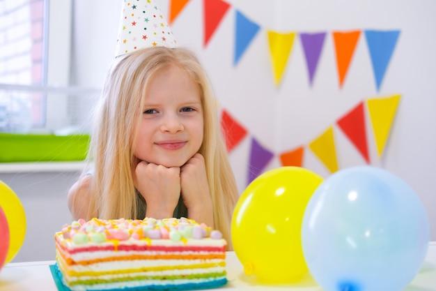 Het blonde kaukasische meisje zit zorgvuldig en dromerig aan feestelijke lijst dichtbij de cake van de verjaardagsregenboog en doet een wens. camera kijken. kleurrijke achtergrond met ballonnen Premium Foto
