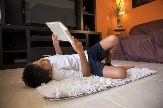 Het boek dat van de jongenslezing op een mat thuis ligt Premium Foto