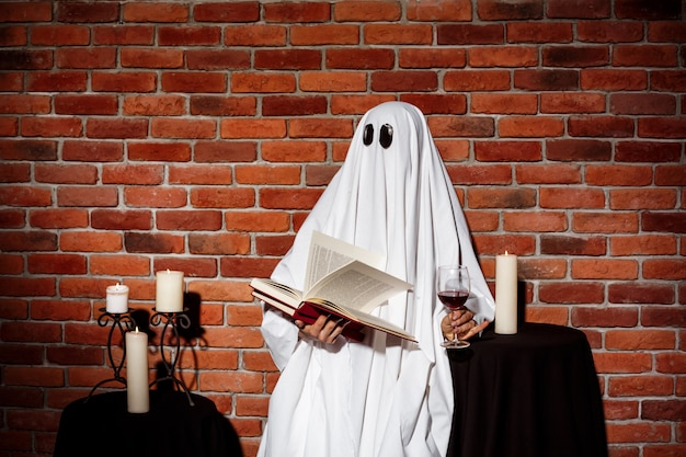 Het boek en de wijn van de spookholding over bakstenen muur. halloween feest. Gratis Foto