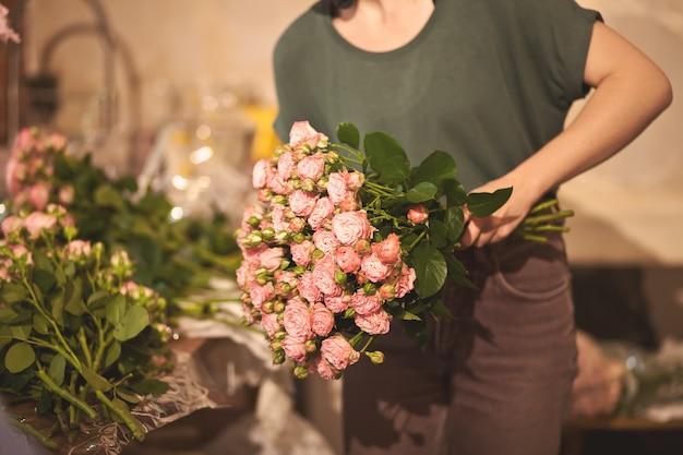 Het boeket van de bloemistholding van kleurrijke bloemen in een bloem slaan op. Premium Foto