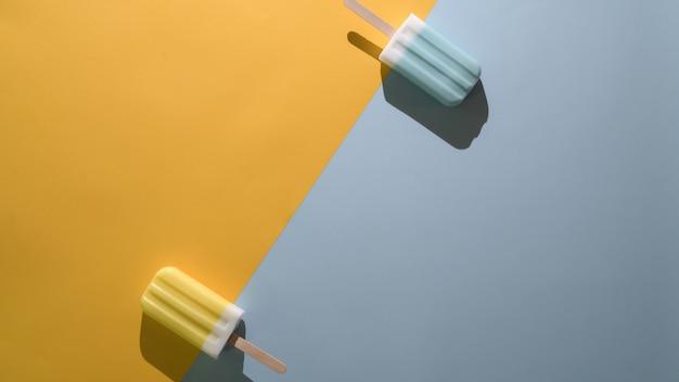 Het bovenaanzicht van ijslollys van het limoen en de blauwe frambozensmaak en exemplaarruimte op vlakte leggen gele en blauwe achtergrond Premium Foto