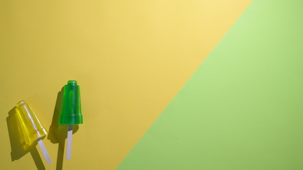 Het bovenaanzicht van limoen en citroensmaakijslollys en exemplaarruimte op vlakte legt gele en groene achtergrond Premium Foto
