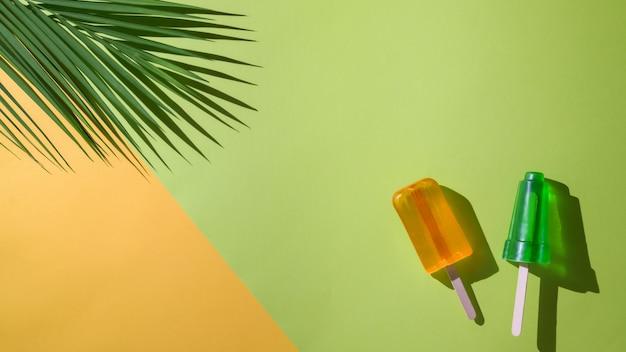 Het bovenaanzicht van limoen en sinaasappelsmaakijslollys, palmblad en exemplaarruimte op vlakte legt gele en groene achtergrond Premium Foto