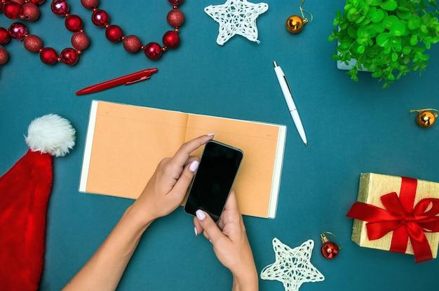 Het bovenaanzicht van vrouwelijke handen met telefoon en kerstversieringen Gratis Foto