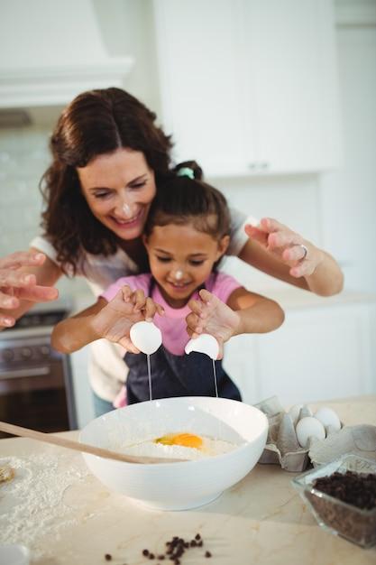 Het brekende ei van de moeder en van de dochter in kom terwijl het voorbereiden van koekje Premium Foto