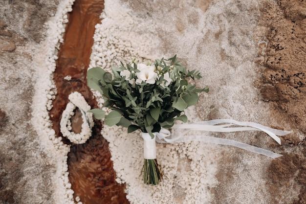 Het bruidsboeket rust op een zoute textuur.het decor op de bruiloft. Premium Foto