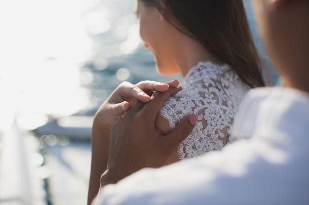 Het bruidspaar koestert op een jacht. schoonheidsbruid met bruidegom. Premium Foto