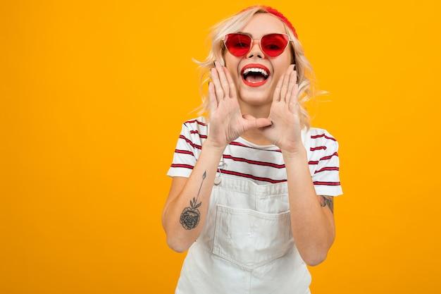 Het charmante sexy blondemeisje in een modieuze blik schreeuwt iets op geel Premium Foto