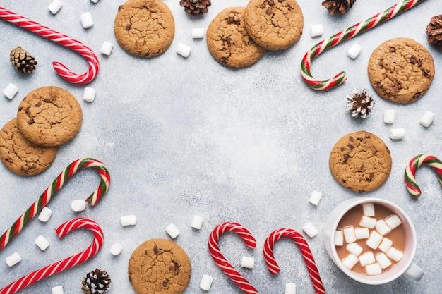 Het chocoladeschilferkoekje, kerstrietkaramel cup cacao en marshmallowkegels decoraties op een grijs. copyspace frame. Premium Foto
