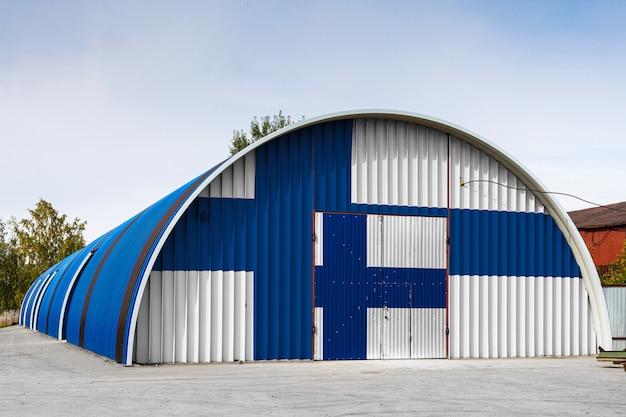 Het close-up van de nationale vlag van finland schilderde op de metaalmuur van een groot pakhuis het gesloten grondgebied tegen blauwe hemel. het concept van opslag van goederen, toegang tot een afgesloten ruimte, logistiek Premium Foto
