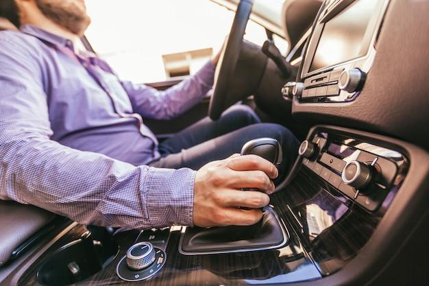 Het close-up van een mannetje dient een moderne auto in Premium Foto