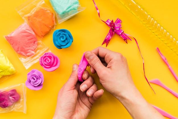Het close-up van een persoon die kleurrijke klei maakt nam op gele achtergrond toe Gratis Foto